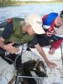 Onneliset kalamiehet ja 5,5kg kala veneen pohjalla